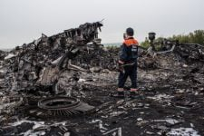 GRABOVKA, UKRAINE - JULY 18: An emergency services worker photographs debris from an Air Malaysia plane crash on July 18, 2014 in Grabovka, Ukraine. Air Malaysia flight MH17 travelling from Amsterdam to Kuala Lumpur crashed yesterday on the Ukraine/Russia border near the town of Shaktersk. The Boeing 777 was carrying 298 people including crew members, the majority of the passengers being Dutch nationals, believed to be at least 173, 44 Malaysians, 27 Australians, 12 Indonesians and 9 Britons. It has been speculated that the passenger aircraft was shot down by a surface to air missile by warring factions in the region.  (Photo by Brendan Hoffman/Getty Images)