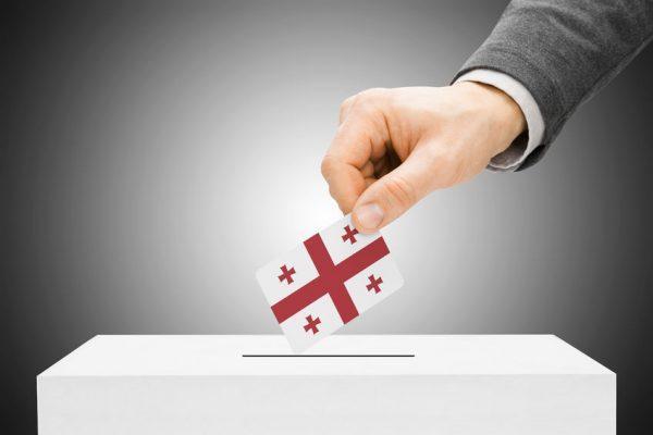 33591605 - voting concept - male inserting flag into ballot box - georgia