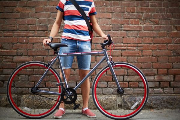 21223634 - close-up of guy with bicycle against brick wall