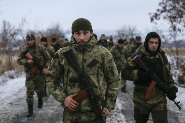 """Pro-Russian separatists from the Chechen """"Death"""" battalion walk during a training exercise in the territory controlled by the self-proclaimed Donetsk People's Republic, eastern Ukraine, December 8, 2014. Chanting """"Allahu Akbar"""" (God is greatest), dozens of armed men in camouflage uniforms from Russia's republic of Chechnya train in snow in a camp in the rebel-held east Ukraine. They say their """"Death"""" unit fighting Ukrainian forces has 300 people, mostly former state security troops in the mainly-Muslim region where Moscow waged two wars against Islamic insurgents and which is now run by a Kremlin-backed strongman. Picture taken December 8, 2014. REUTERS/Maxim Shemetov (UKRAINE - Tags: POLITICS CIVIL UNREST CONFLICT)"""