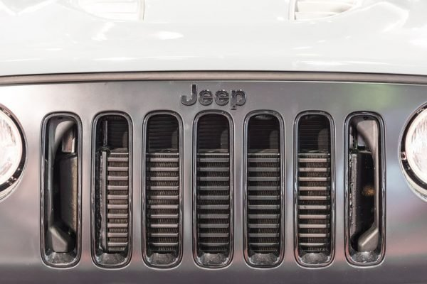 35543038 - bucharest, romania - october 31, 2014: jeep wrangler unlimited sign close up. the wrangler is a direct descendant of the world war ii and is manufactured by american automaker chrysler.