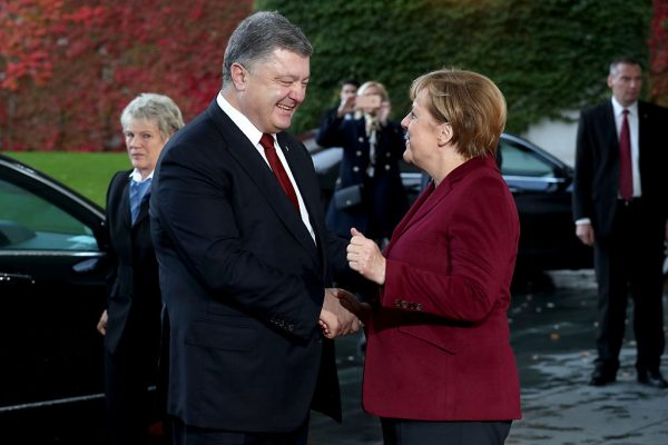 BERLIN, GERMANY - OCTOBER 19:  German Chancellor Angela Merkel (R) greets Ukrainian President Petro Poroshenko upon his arrival to discuss the Ukrainian peace process at the Chancellery on October 19, 2016 in Berlin, Germany. The leaders of Russia, Ukraine, France and Germany, known as the Normandy Four, are meeting to discuss implementation of the peace plan known as the Minsk Protocol, a roadmap for resolving the conflict in Ukraine after Russian forces invaded in 2014 and annexed the peninsula of Crimea. The United States has threatened renewed sanctions on Russia if the country did not either implement the plan in the coming months or arrive at a plan on how to do so.  (Photo by Sean Gallup/Getty Images)