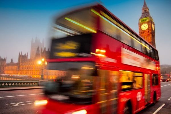 18624014 - big ben with the houses of parliament and a red double-decker bus passing at dusk