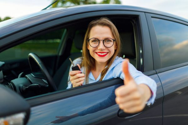 63550630 - young happy woman sitting in a car with thumb up - concept of buying a used car or a rental car