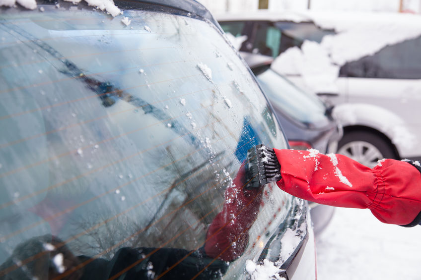 51338422 - woman is removing snow from car window with ice scraper in winter.