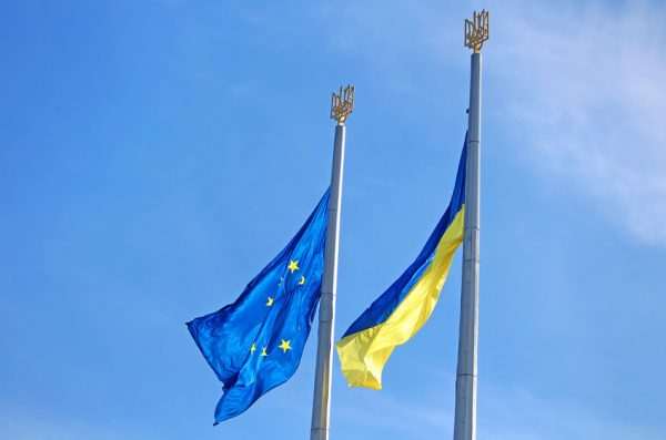 53112655 - flags of the eu and ukraine on the flagpole