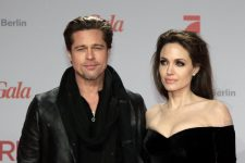 """U.S. actors Angelina Jolie (R) and Brad Pitt pose for pictures as they arrive for the European premiere of the movie """"The Tourist"""" in Berlin"""
