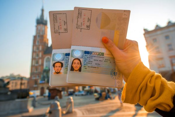 49040003 - female hands holding ukrainian passports with shengen visas on the krakow city center background. traveling to europe from post-soviet countries concept