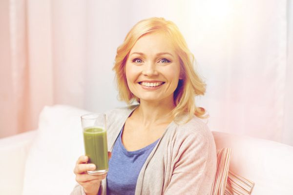 65111674 - healthy eating, vegetarian food, dieting, detox and people concept - smiling middle aged woman drinking green fresh vegetable juice or smoothie from glass at home