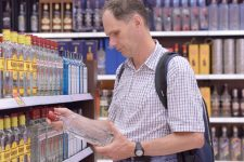 24111028 - kiev, ukraine - june 22, 2013: man selects alcohol in a duty free shop in the airport of kiev, ukraine on june 22, 2013. alcohol is the most popular position in the assortment of duty free shops