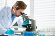 44011734 - scientist looking through a microscope in a laboratory