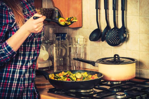 58520385 - closeup of human in kitchen cooking stir fry frozen vegetables. person frying making delicious risotto. dinner food meal.