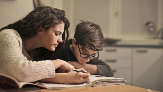 Жінка виконує домашня завдання з дитиною