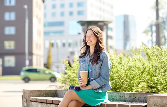 Дівчина з горнятком кави усміхається